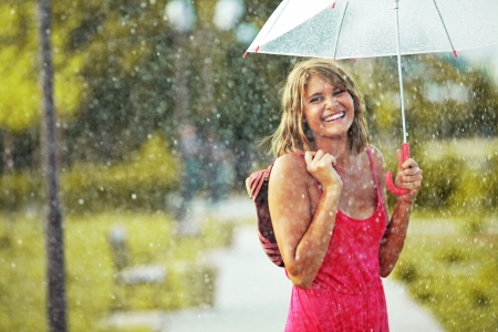 wet dress: Portrait of beautiful young girl walking with umbrella under rain