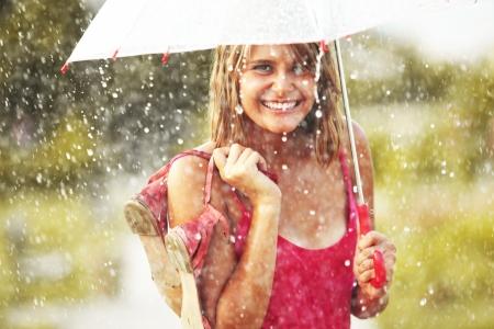 Portret van mooie jonge meisje lopen met paraplu onder regen Stockfoto