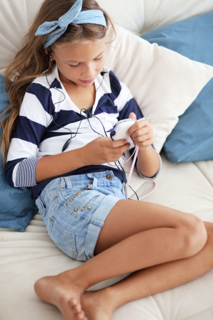 8 years: Child listening music on the sofa at home Stock Photo