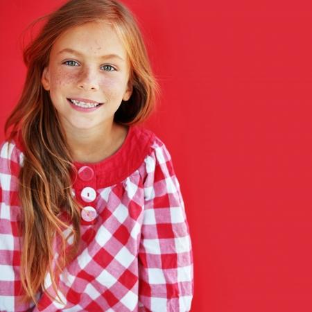 happy young: Ni�o pelirrojo lindo en fondo rojo Foto de archivo