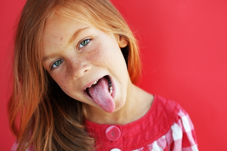 舌: 赤い背景の上にかわいい赤毛子供 写真素材