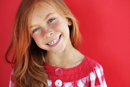 Nette rothaarige Kind auf rotem Hintergrund