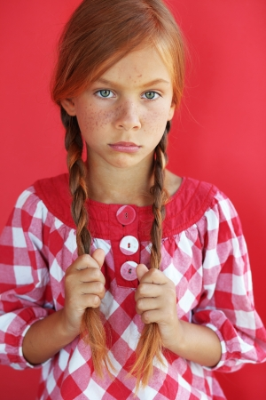 freckles: Cute redheaded child on red background Stock Photo