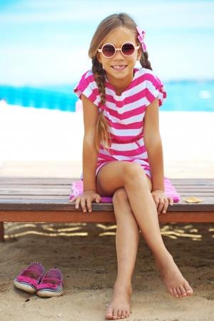 jovem: Criança que descansa na praia do verão Imagens