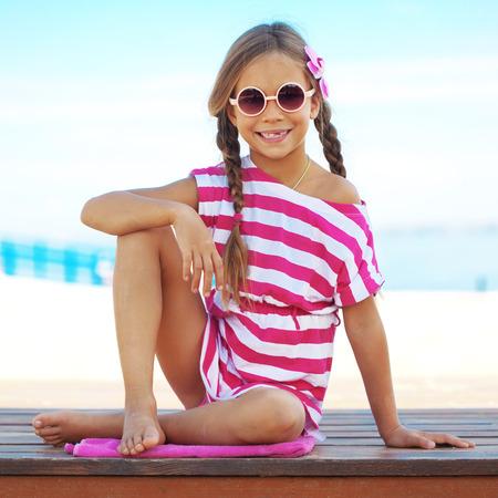 klein meisje op strand: Kind rusten in de zomer strand Stockfoto