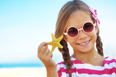 preteens beach: Child holding seashell at the summer beach Stock Photo