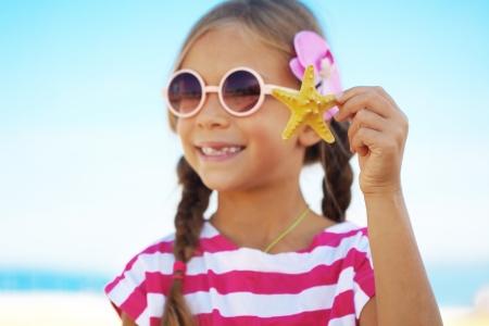 Child holding seashell at the summer beach photo