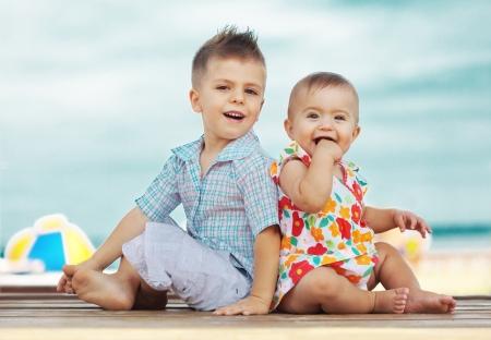 Portret van kinderen die op het strand in de zomer Stockfoto