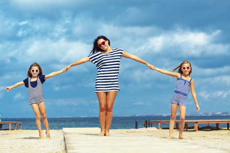 Mother with two daughters resting at the beach in summer Stock Photo - 22214686