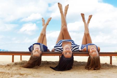 夏のビーチで休んで 2 人の娘を持つ母 写真素材