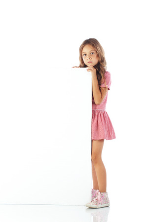 Portrait of a school girl with blank board for custom text photo