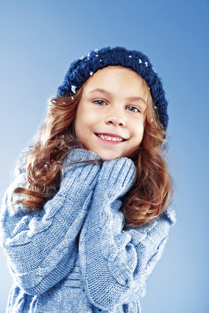 Winter portrait of cute little girl wearing warm cosy clothes studio shot with snow Stock Photo - 22443743