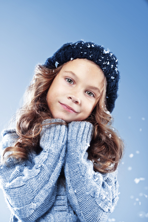 Winter portrait of cute little girl wearing warm cosy clothes studio shot with snow Stock Photo - 22443744