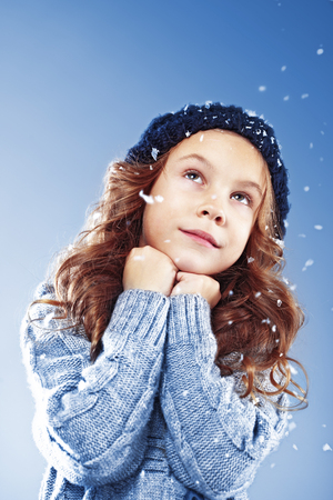 Winter portrait of cute little girl wearing warm cosy clothes studio shot with snow Stock Photo - 22443745