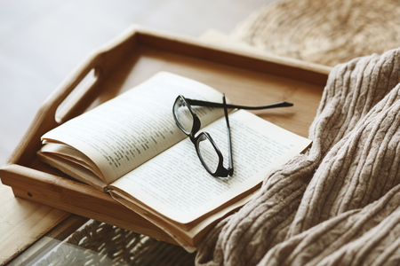 still life: Warm knitted sweater and a book on a wooden tray Stock Photo