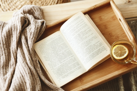 domestic scene: Warm knitted sweater and a book on a wooden tray Stock Photo