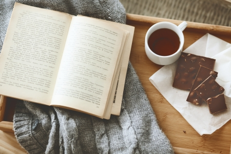 Warm knitted sweater and a book on a wooden tray Stock Photo