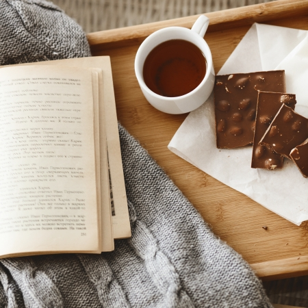 tea house: Warm knitted sweater and a book on a wooden tray Stock Photo