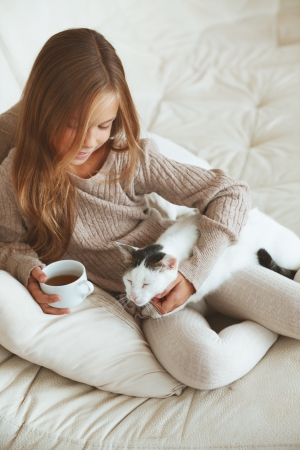 Child wearing sweater and drinking tea at home photo