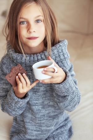 Niño con suéter y beber té en casa Foto de archivo - 22461237