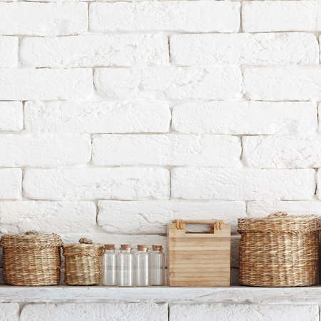 Decorative shelf on white brick wall with vintage bottles and wicker jars on it Stock Photo - 22486460