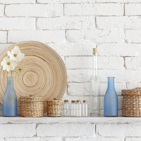 Decorative shelf on white brick wall with vintage bottles and wicker jars on it Stock Photo - 22486461