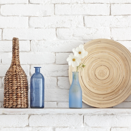 Decorative shelf on white brick wall with vintage bottles and wicker jars on it Stock Photo - 22486462