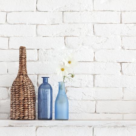 ビンテージ ボトルとそれを枝編み細工品の jar ファイルと白いレンガ壁に装飾的な棚