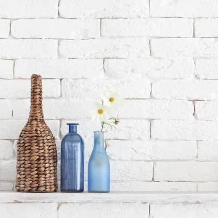 glass brick: Decorative shelf on white brick wall with vintage bottles and wicker jars on it