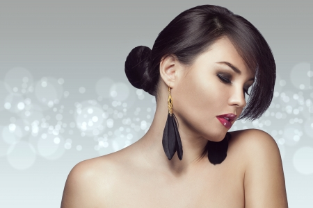 earring: Portrait of beautiful woman with perfect make up over party lights Stock Photo
