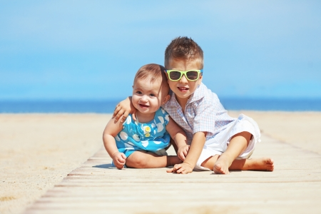 Portrait of kids resting on the beach in summer photo