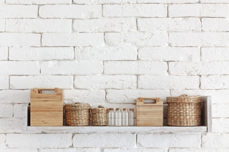 Decorative shelf on white brick wall with vintage bottles and wicker jars on it Stock Photo - 23247171