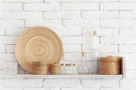 Decorative shelf on white brick wall with vintage bottles and wicker jars on it Stock Photo - 23247170