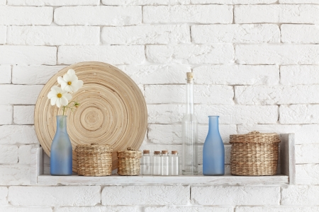 Decorative shelf on white brick wall with vintage bottles and wicker jars on it Stock Photo - 23247211