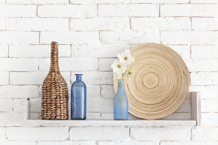 Decorative shelf on white brick wall with vintage bottles and wicker jars on it photo