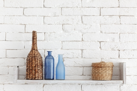 Decorative shelf on white brick wall with vintage bottles and wicker jars on it Stock Photo - 23247207