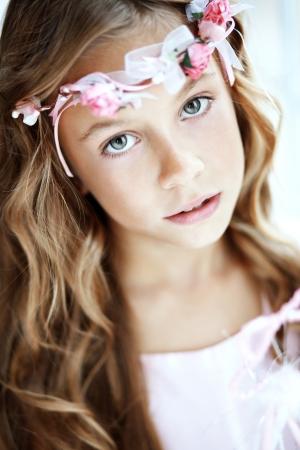 Portrait of beautiful little girl wearing floral wreath photo
