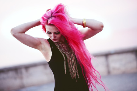 Street portrait of bright teenage girl with vivid pink hair photo