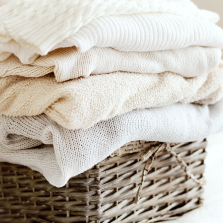Stack of cozy knitted sweaters in wicker backet