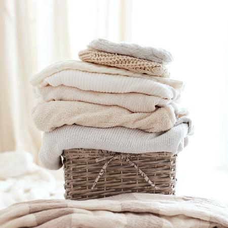 Pila de suéteres tejidos acogedoras en backet de mimbre
