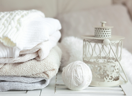 warm cloth: Stack of cozy knitted sweaters and lantern on a table Stock Photo