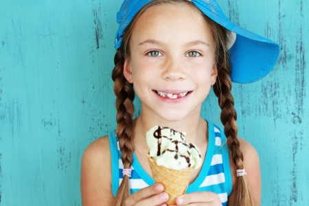 over eating: Portrait of 7 years old kid girl eating tasty ice cream over blue Stock Photo