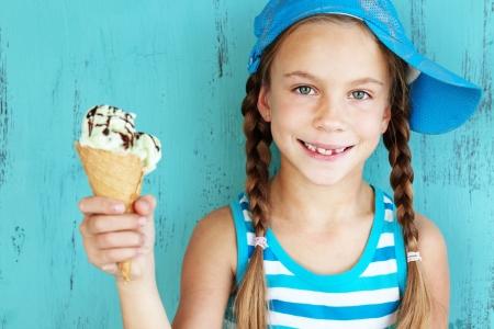 sabroso: Retrato de 7 a�os de la muchacha del cabrito de comer sabroso helado sobre azul