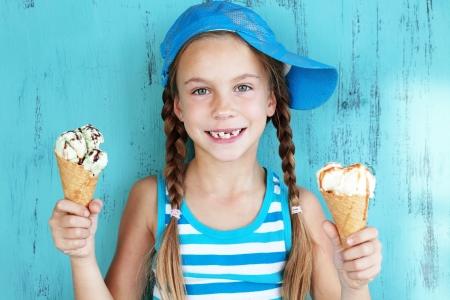青でおいしいアイスクリームを食べての 7 歳子供少女の肖像画
