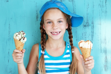 Portrait of 7 years old kid girl eating tasty ice cream over blue Stock Photo