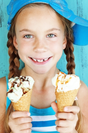 7 years old: Portrait of 7 years old kid girl eating tasty ice cream over blue Stock Photo