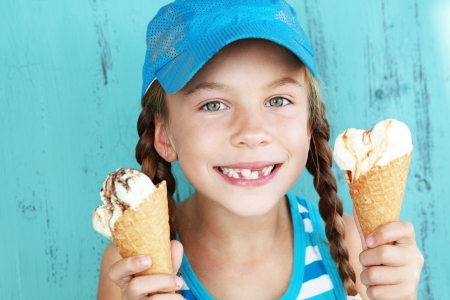 ice age: Portrait of 7 years old kid girl eating tasty ice cream over blue Stock Photo