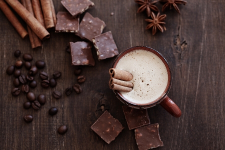 Cup of hot coffe with cinnamon sticks on vintage wooden background, selective focus photo