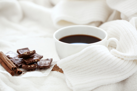 Cup of hot coffe with cinnamon sticks with knitted cozy sweater, selective focus photo