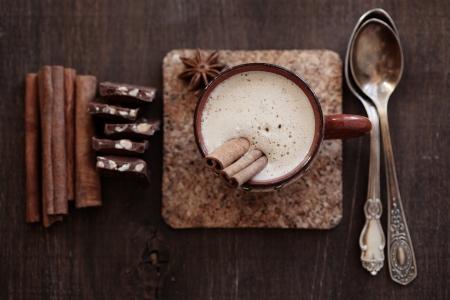 Kop van hete koffie met kaneel op vintage houten achtergrond, selectieve aandacht